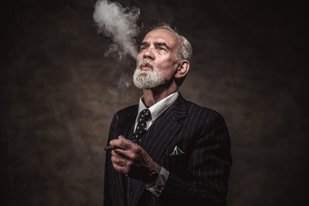 Cigar smoking characteristic senior business man with gray hair and beard wearing blue striped suit and tie. Against brown wall.
