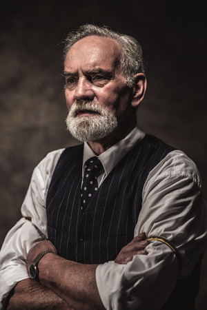 Characteristic senior business man with gray hair and beard wearing blue striped gilet and tie. Against brown wall.