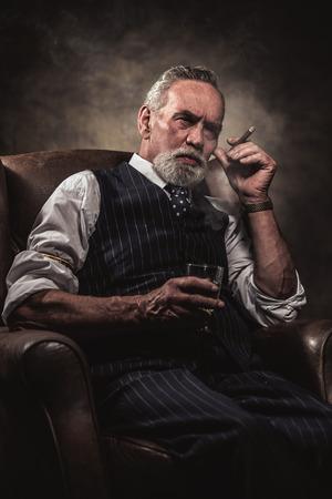 In Stuhl Senior Business Mann mit Zigarre und Whisky. Graue Haare und Bart tragen blau gestreiften Weste und Krawatte. Gegen braunen Wand. Standard-Bild - 32035111