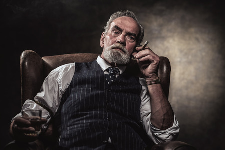 In chair sitting senior business man with cigar and whisky. Gray hair and beard wearing blue striped gilet and tie. Against brown wall.