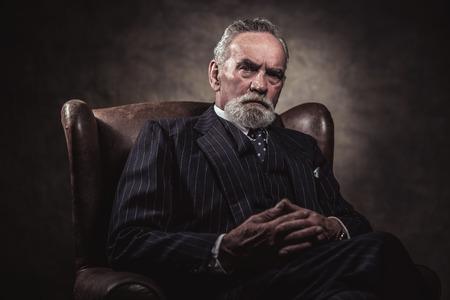 In Stuhl charakteristischen älterer Geschäftsmann. Graue Haare und Bart tragen blau gestreiften Anzug und Krawatte. Gegen braunen Wand. Standard-Bild - 32034297