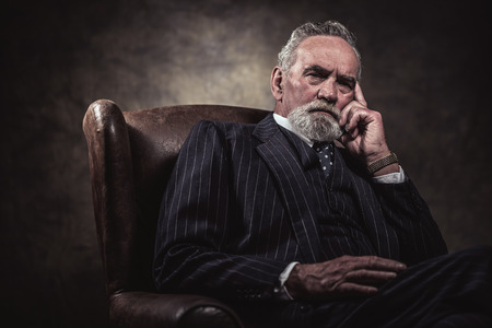 In chair sitting characteristic senior business man. Gray hair and beard wearing blue striped suit and tie. Against brown wall. Stockfoto