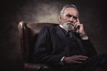 V křesle sedí charakteristickou senior business man. Šedé vlasy a vousy na sobě modré pruhované oblek a kravatu. Proti hnědé stěny.