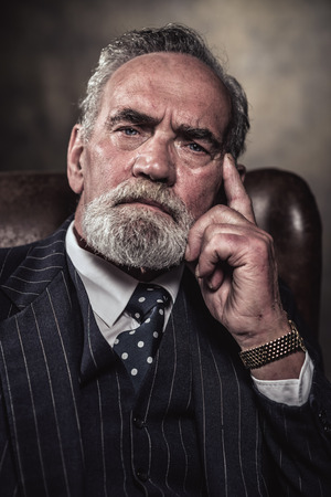 In chair sitting characteristic senior business man. Gray hair and beard wearing blue striped suit and tie. Against brown wall. Stock Photo