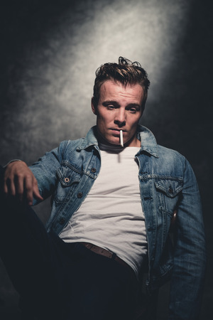 rebellion: Cigarette smoking retro fifties cool rebellion fashion man wearing white shirt and jeans jacket. Gray wall.