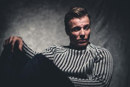 Retro fifties cool rebellion fashion man wearing striped woolen sweater. Gray wall.