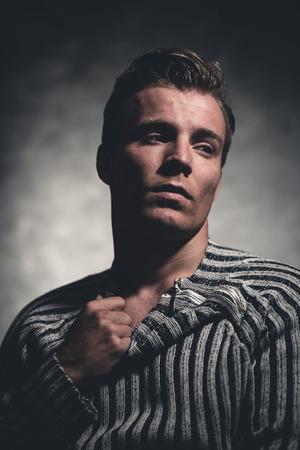 rebellion: Retro fifties cool rebellion fashion man wearing striped woolen sweater. Gray wall.