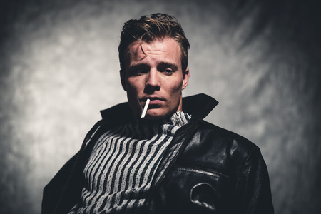 rebellion: Cigarette smoking retro fifties cool rebellion fashion man wearing striped woolen sweater and black leather jacket. Gray wall. Stock Photo