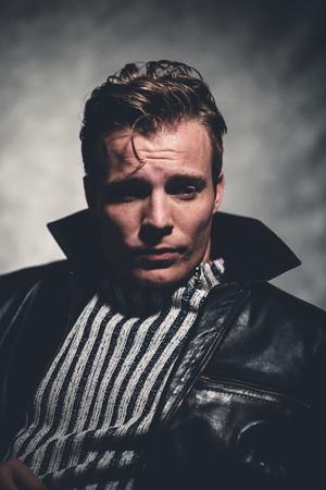 Retro fifties cool rebellion fashion man wearing striped woolen sweater and black leather jacket. Gray wall. 스톡 콘텐츠