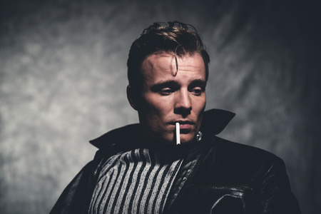 Cigarette smoking retro fifties cool rebellion fashion man wearing striped woolen sweater and black leather jacket. Gray wall. 스톡 콘텐츠