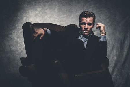 Cigarette smoking retro fifties cool business fashion man wearing black suit. Sitting in leather chair. Gray wall. photo