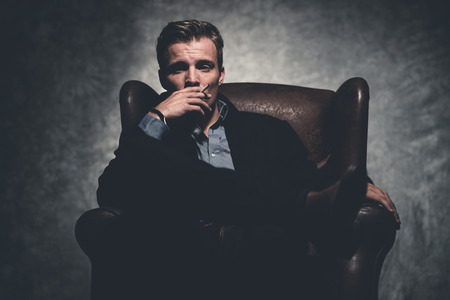 Cigarette smoking retro fifties cool business fashion man wearing black suit. Sitting in leather chair. Gray wall. Standard-Bild