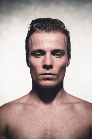 belleza masculina: Apuesto joven con mancha de peinar el pelo rubio. Tiro de la belleza. Retrato del estudio. Foto de archivo