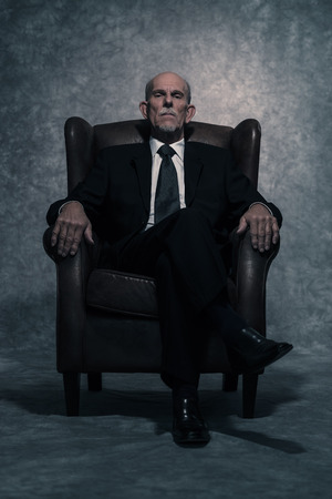 In leather chair sitting senior businessman with gray beard wearing dark suit and tie. Against grey wall. Standard-Bild