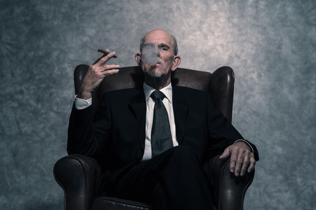 Cigar smoking senior businessman with gray beard wearing dark suit and tie. Sitting in leather chair. Against grey wall. Stock Photo
