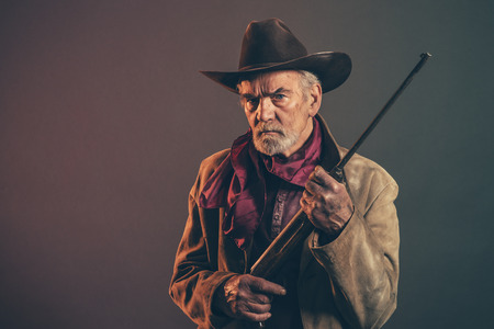 Old rough western cowboy with gray beard and brown hat holding rifle. Low key studio shot.