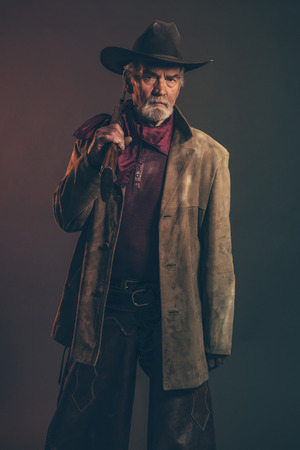 Old rough western cowboy with gray beard and brown hat holding rifle. Low key studio shot. photo