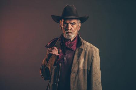 Old grobe Western Cowboy mit grauem Bart und braunen Hut hält das Gewehr. Low key-Studio. Standard-Bild - 32954775