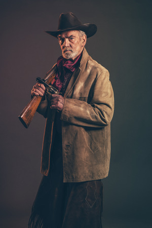 Old rough western cowboy with gray beard and brown hat holding rifle and revolver. Low key studio shot.