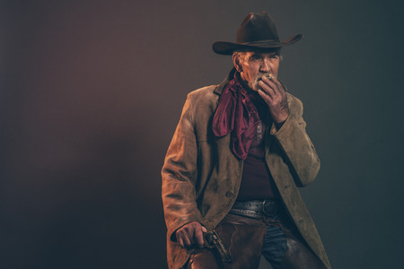 Old rough western cowboy with gray beard and brown hat smoking a cigarette. Low key studio shot. Stock Photo