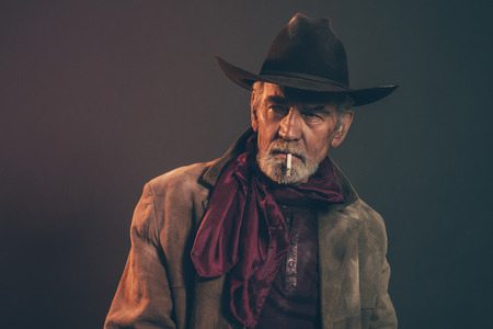 western culture: Old rough western cowboy with gray beard and brown hat smoking a cigarette. Low key studio shot. Stock Photo