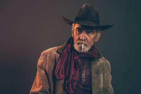 hombre con sombrero: Viejo vaquero occidental rugosa con barba gris y un sombrero marrón fumar un cigarrillo. Tiro bajo estudio clave.