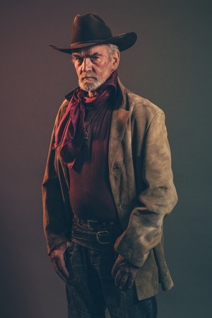 western clothing: Old rough western cowboy with gray beard and brown hat. Low key studio shot.