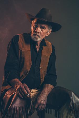 Cigarette smoking old rough western cowboy with gray beard and brown hat. Low key studio shot. Standard-Bild