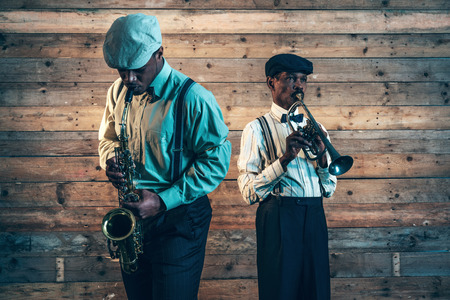 Two african american jazz musicians playing trumpet and saxophone. Standing in front of old wooden wall. 스톡 콘텐츠