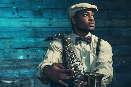 saxofón: Músico de jazz africano americano con el saxofón en frente de la vieja pared de madera.