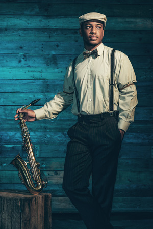 african sax: African american jazz musician with saxophone in front of old wooden wall.