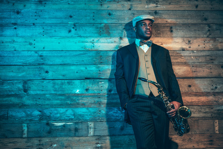 african sax: Vintage african american jazz musician with saxophone in front of old wooden wall. Wearing suit and cap.