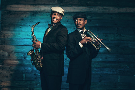 Two vintage african american jazz musicians with trumpet and saxophone in front of old wooden wall. Wearing black suit and cap. 스톡 콘텐츠