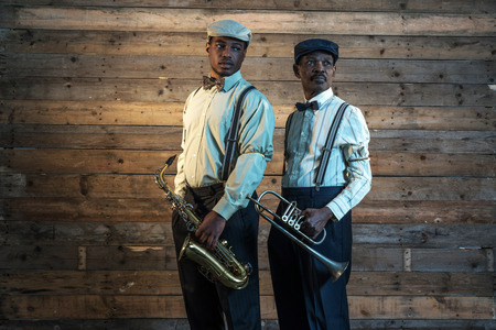 african sax: Two african american jazz musicians with trumpet and saxophone standing in front of old wooden wall.
