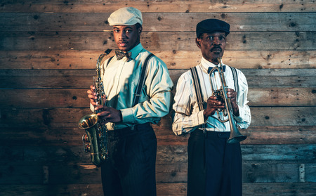 Two african american jazz musicians with trumpet and saxophone standing in front of old wooden wall. photo