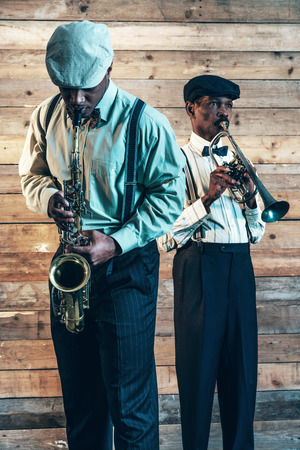 Two african american jazz musicians playing trumpet and saxophone. Standing in front of old wooden wall. 版權商用圖片