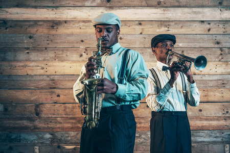 Two african american jazz musicians playing trumpet and saxophone. Standing in front of old wooden wall. Stock Photo