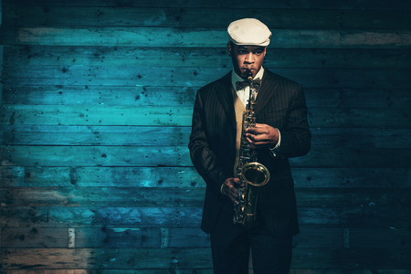 Vintage african american jazz musician with saxophone in front of old wooden wall. Wearing suit and cap.