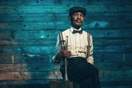jazz musician: Vintage african american senior jazz musician with trumpet in front of old wooden wall. Wearing suit and cap.