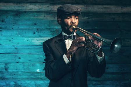 Vintage african american senior jazz musician with trumpet in front of old wooden wall. Wearing black suit and cap. Standard-Bild