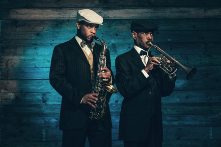 Two vintage african american jazz musicians with trumpet and saxophone in front of old wooden wall. Wearing black suit and cap. photo