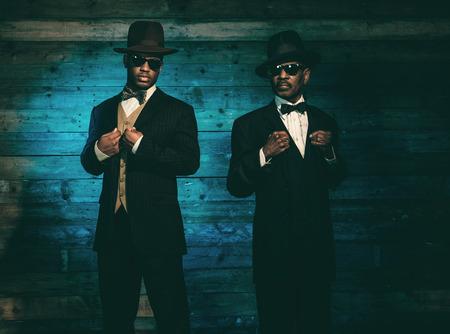 modelos negras: Dos g�ngsteres africano americano de la vendimia delante de la vieja pared de madera. El uso de gafas de sol negras con traje y sombrero. Foto de archivo