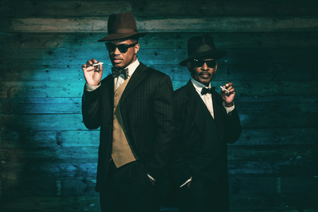 Two vintage african american gangsters smoking cigarette in front of old wooden wall. Wearing black sunglasses with suit and hat. Stockfoto