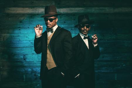 Zwei Vintage African American Gangster Rauchen von Zigaretten vor der alten Holzwand. Trägt schwarze Sonnenbrille mit Anzug und Hut. Standard-Bild - 33998924