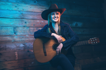 female singer: Cowgirl country singer with acoustic guitar. Wearing blue jeans and brown hat. In front of wooden wall.