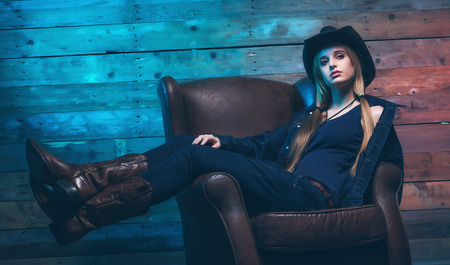 Cowgirl Wearing blue jeans and brown hat. Sitting on leather chair. In front of wooden wall. photo