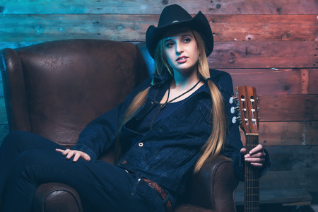 Cowgirl country singer with acoustic guitar. Sitting on leather chair. Wearing blue jeans and brown hat. In front of wooden wall. photo
