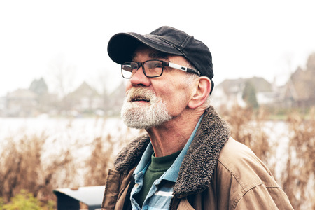 people portraits: Senior man with beard wearing glasses and black cap outdoor in winter landscape with houses in the background.