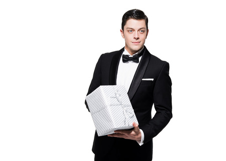 dinner jacket: New years eve fashion man wearing black dinner jacket. Holding silver present. Isolated against white.