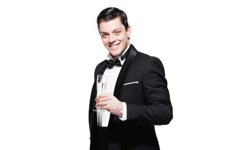 dinner jacket: New years eve fashion man wearing black dinner jacket. Holding glass of champagne. Isolated against white.